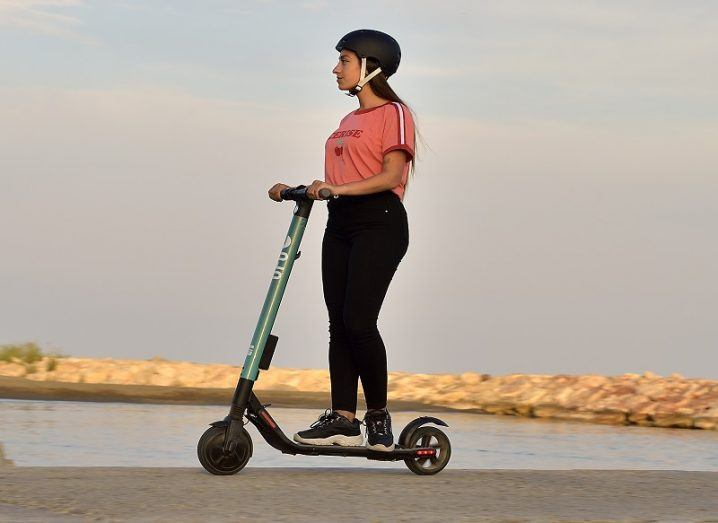 A woman in a pink t-shirt and black jeans riding a SEAT e-scooter along a pier at dusk.