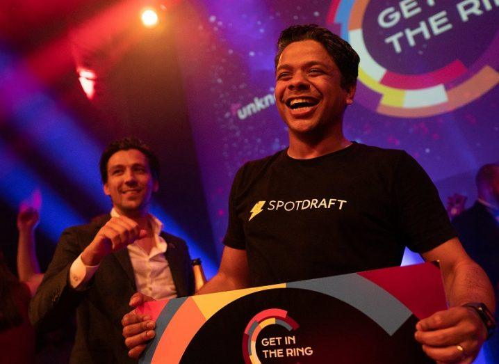 Shashank Bijapur of SpotDraft smiling widely on stage after winning his award.