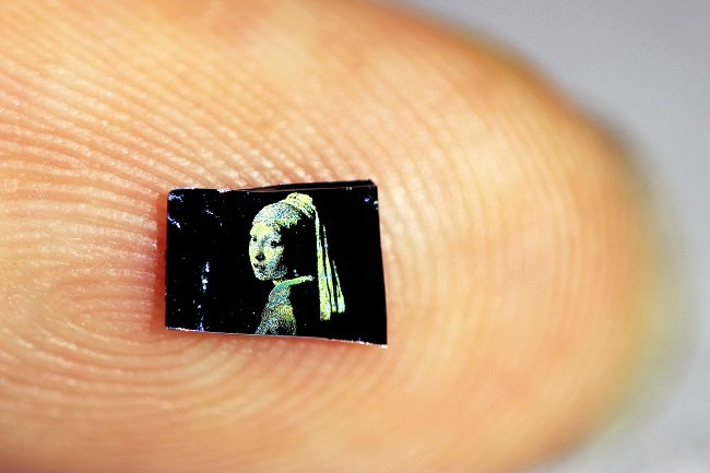 Close-up of a tiny 1mm-wide 'Girl with a Pearl Earring' painting on a person's fingertip.