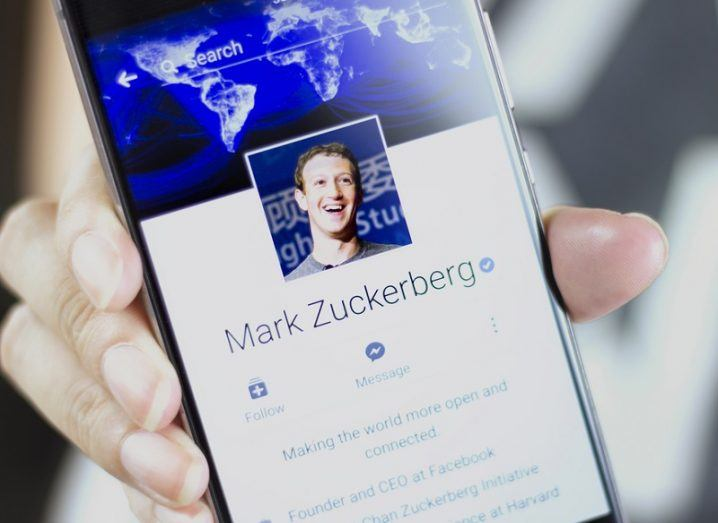Person holding a phone screen showing the Facebook profile of Mark Zuckerberg.