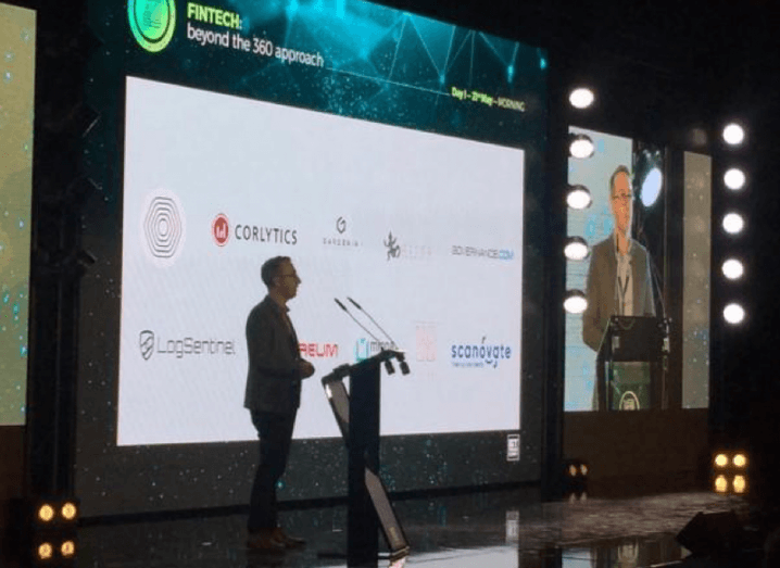 A man presents on stage in front of a slide bearing the names of different fintech companies.