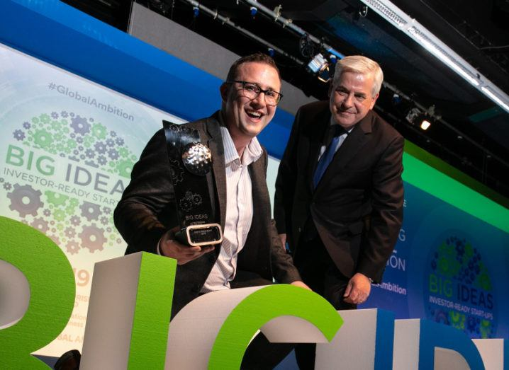 A cheerful smiling man holding a trophy poses for a photo with an older man on a stage emblazoned with the brand 'Big Ideas'.