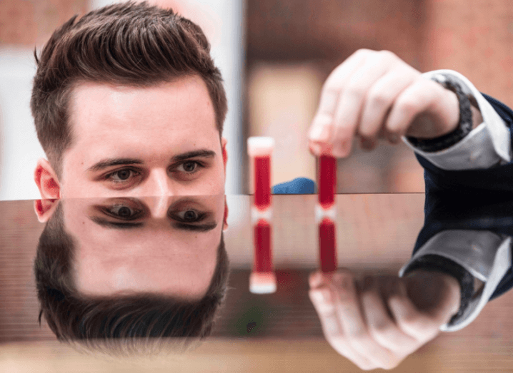 Student Entrepreneur of the Year Christopher McBrearty places blood test vials on a tabletop that reflects his face.