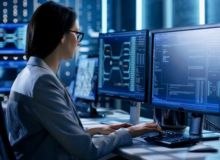 Cybersecurity worker on dual screen computers with coding interface on both screens.