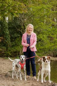blonde woman in light pink blazer smiling broadly as she walks two dogs on leashes in green forest setting.