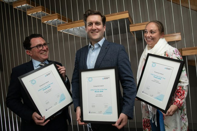 Two men and one woman smile proudly as they hold up certificates they were awarded from Enterprise Ireland.