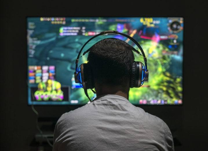 Young gamer playing video game wearing headphones.