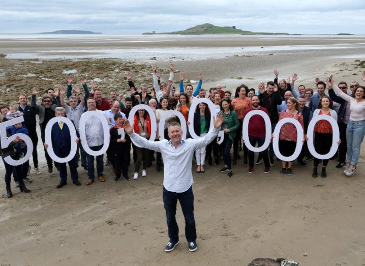 Man standing on beach with workers behind him holding a sign denoting 5 million taxi trips.