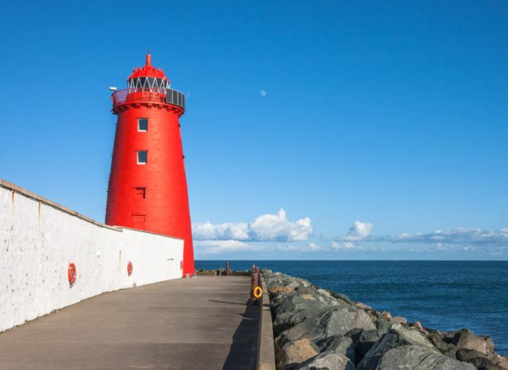 Picture of a red lighthouse beside rocks overlooking Dublin bay.