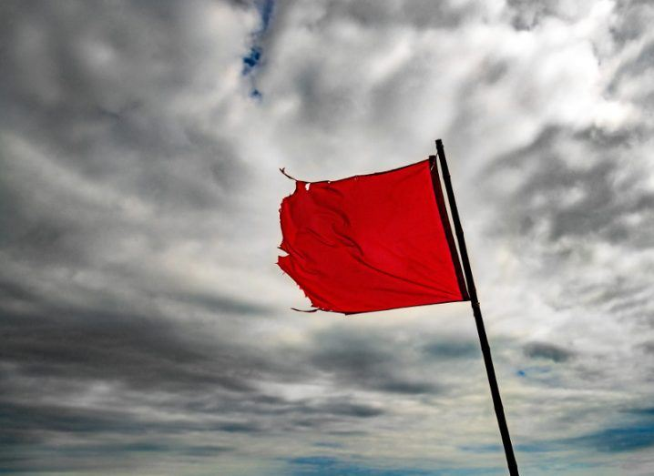 The wind blows a torn red flag under cloudy skies.