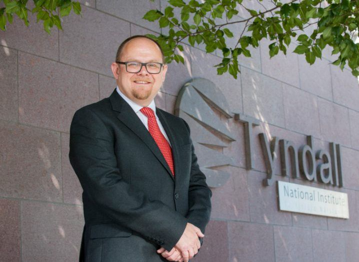 middle-aged man with glasses wearing a suit and standing outside beside a stone wall with a sign for Tyndall National Institute.