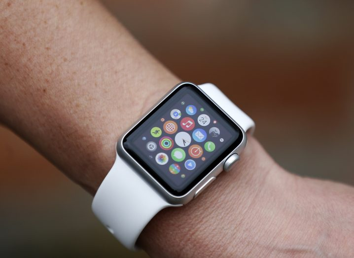 A close-up of a person's wrist, wearing an Apple Watch, with apps visible on the screen.