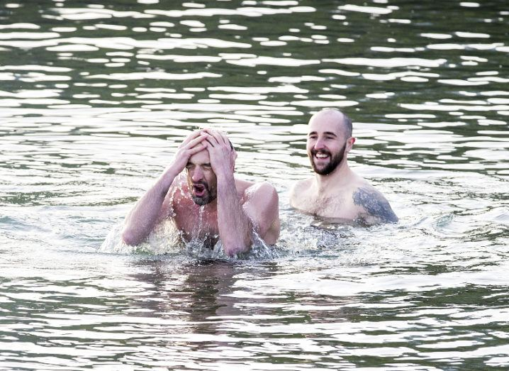 Two bearded men swimming in open water. One is smiling as the other splashes water into his own face.