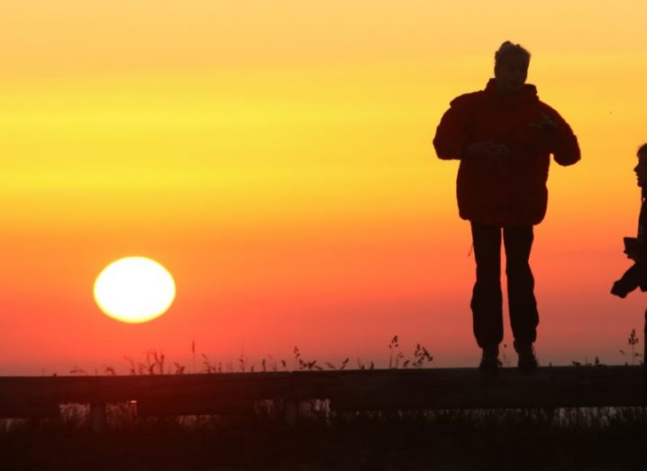 A searing sun is seen on the horizon by a man in silhouette.