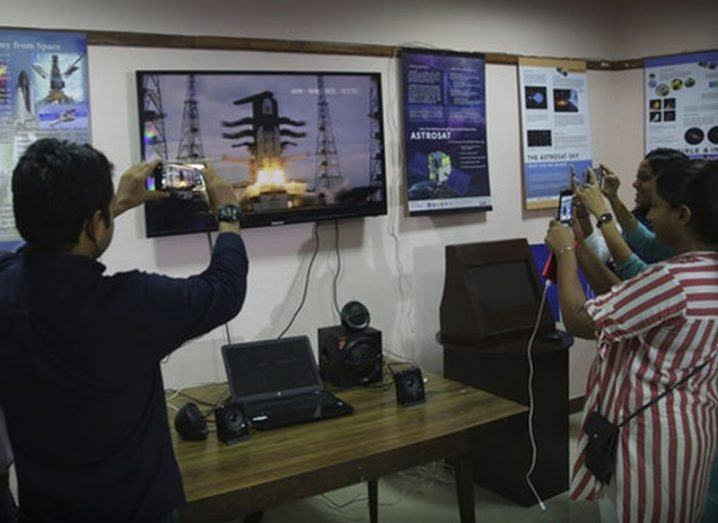 People stand around a TV screen showing the spacecraft launch, holding up their phones to capture pictures and videos.