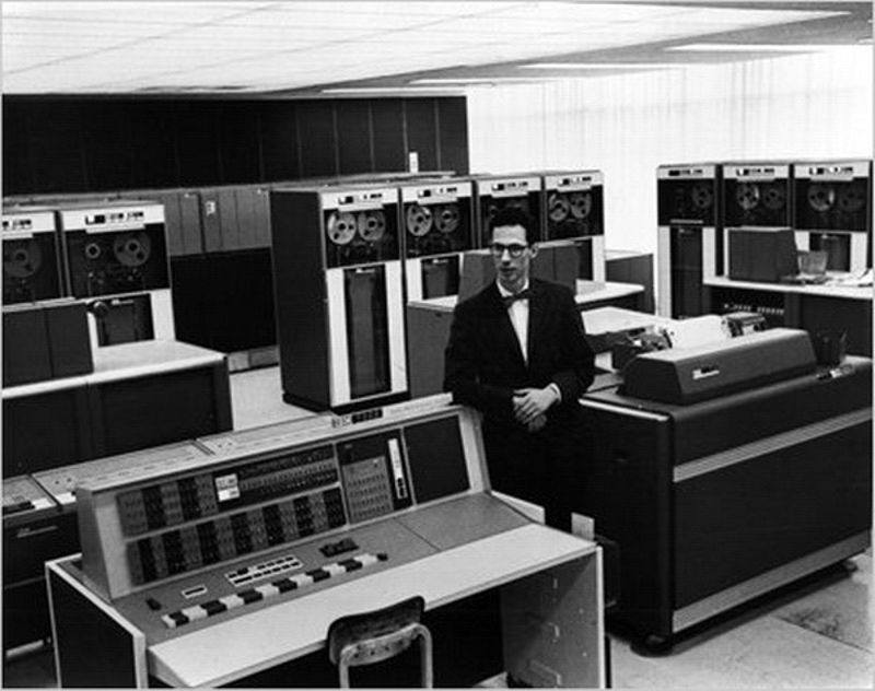Black and white image of Fernando Carbató standing beside a number of old computers in a lab.