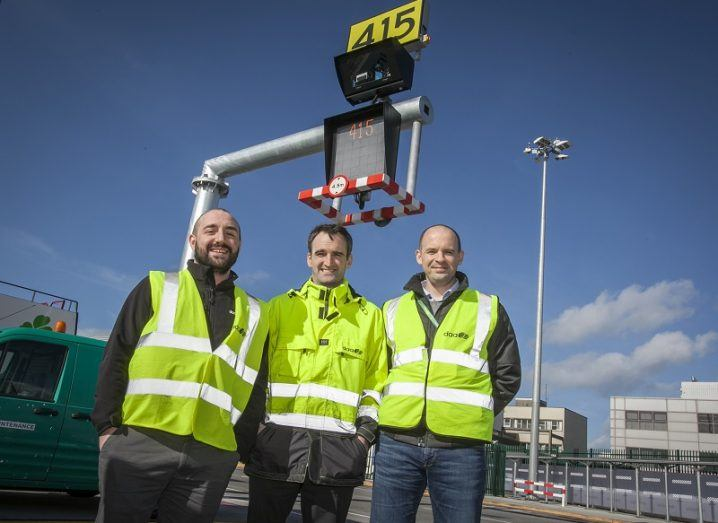 Mark O'Connor, Conor Carroll and Dan Davis in high-vis jackets smiling and standing under the new automatic visual docking guidance system.