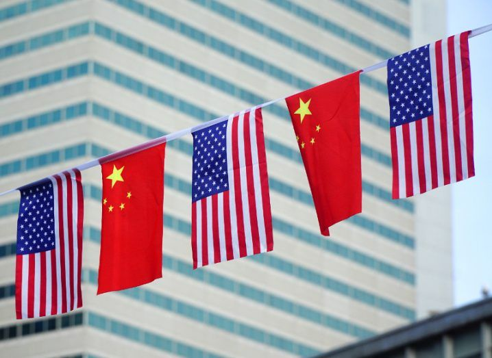 US and Chinese flags hanging on a zip line in front of a towering glass building in the business district of a city.