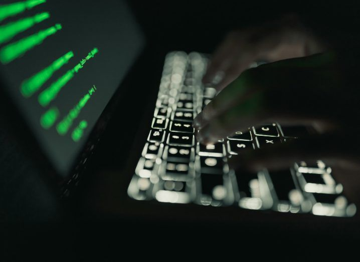 View of illuminated laptop keyboard and the silhouette of hands typing on it. The laptop screen is filled with code in green font.