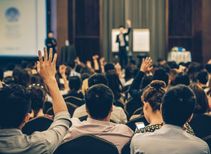 A speaker raises their hand on stage at a conference, and some audience members who are entrepreneurs raise their hands too.