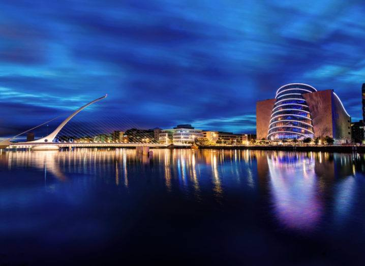 View of Dublin city's financial district, Convention Centre and Liffey River illuminated at night.