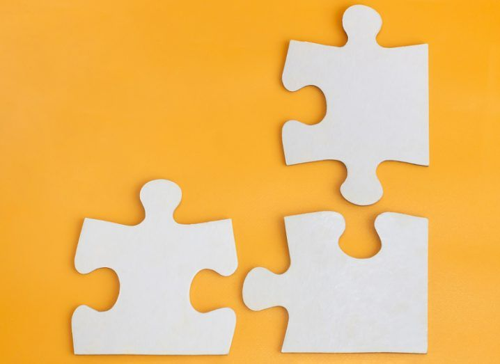 Three white jigsaw pieces separated on an orange background.