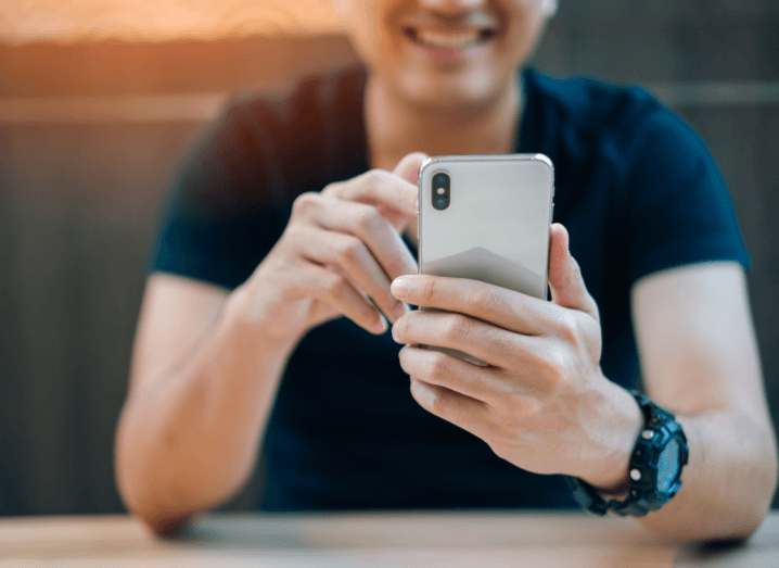 A person in a black t-shirt, wearing a black wristwatch, holding an iPhone X and smiling in a cafe.