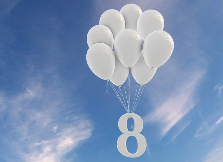 A white number eight ascending into a blue, cloudy sky attached to a clump of white balloons.