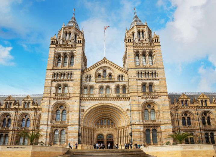 The grand entrance of the Natural History Museum in London, with the UK flag flying above it against a blue sky.