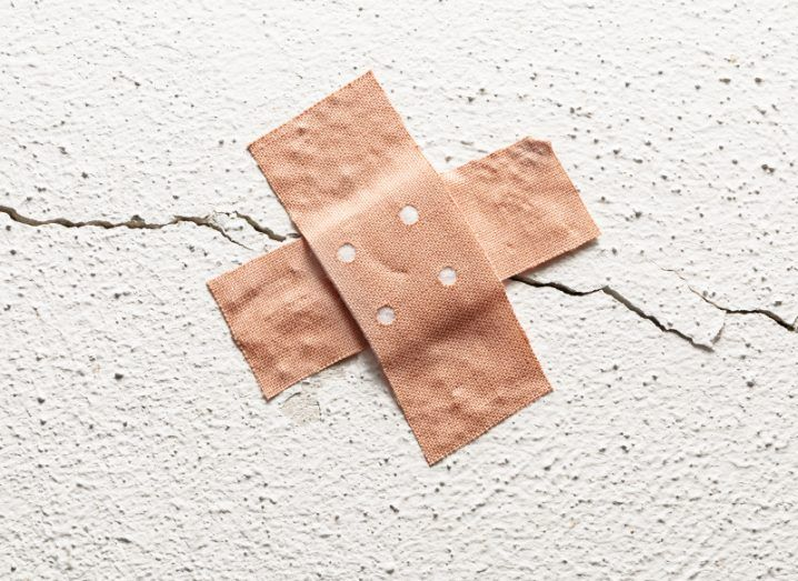 Two band-aid plasters are fixed in a cross shape to a crack in a white plastered wall.