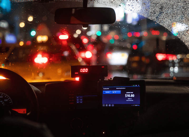 The interior of a taxi on a busy city street at night.