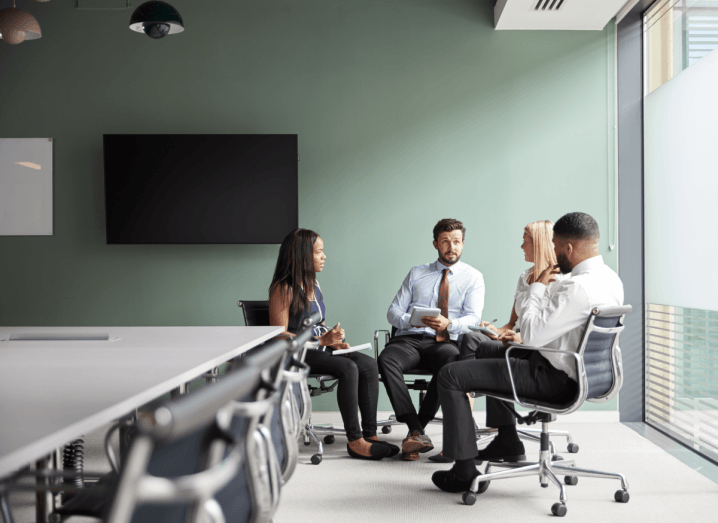A group of four recruiters sitting in a green meeting room having a discussion.