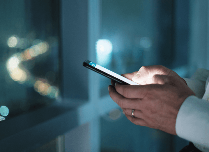 The hands of a business person wearing a white shirt, who is holding a phone and looking at WhatsApp. They are standing in front of the window of a high-rise building at night time.