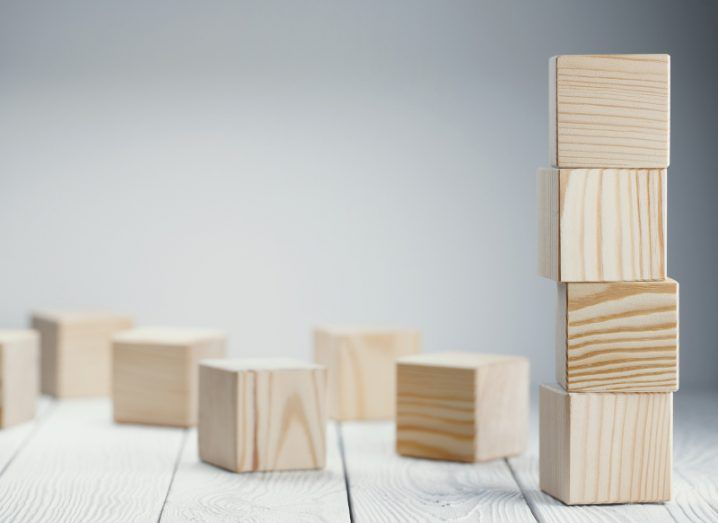 Four wooden blocks piled one on top of the other, surrounded by a scattering of other blocks.
