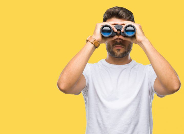 bearded man in white T-shirt holding binoculars against bright yellow background, looking out for key IT trends.