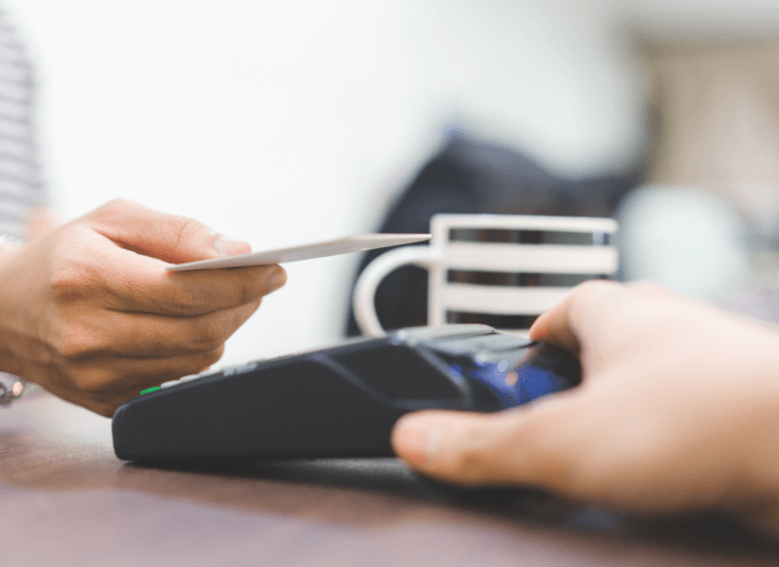The hand of an individual making a contactless payment with a credit or debit card.