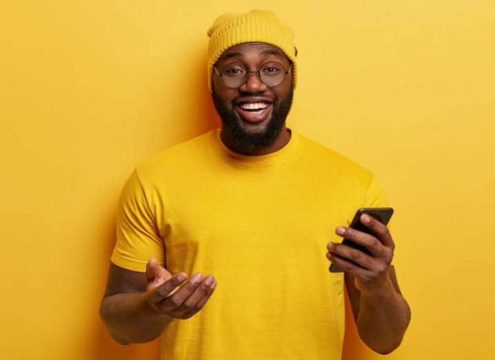 View of happy smiling man in yellow t-shirt and beanie holding his phone against a canary yellow background.