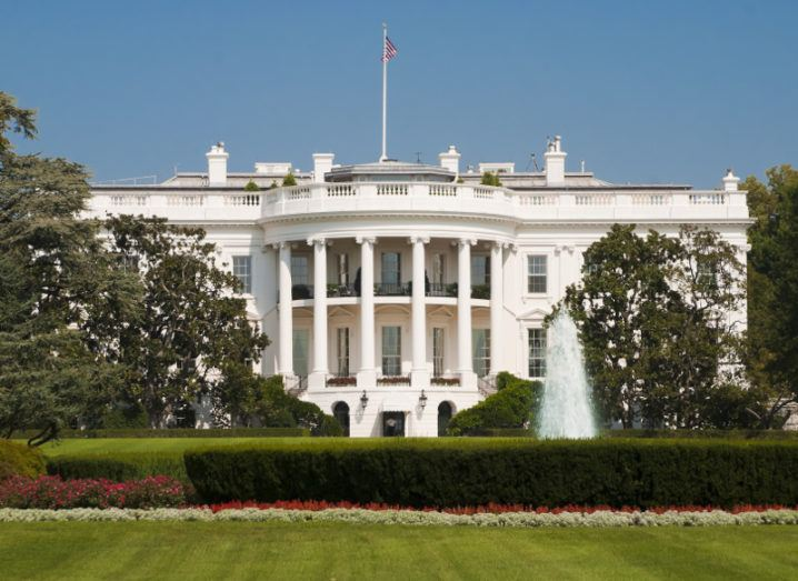 View of the White House façade and manicured lawns on a bright day with US flag flying at full mast over it.