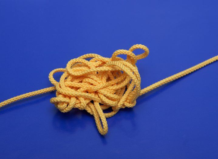 A length of thin yellow rope tangled in a large knot on a royal blue background.