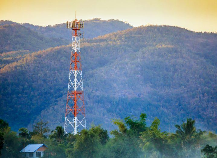 View of telecoms tower standing high against hillside at sunrise.