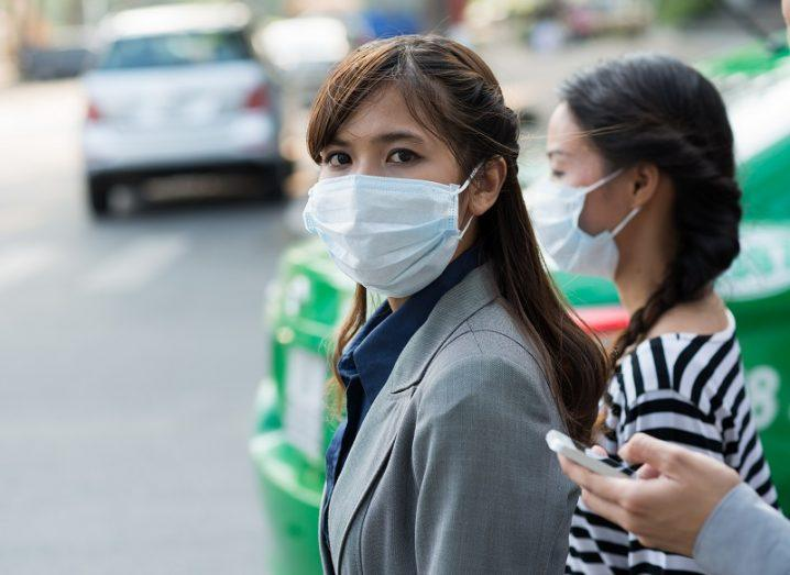 A woman in grey businesswear wearing a white surgical mask on the side of a street while looking at the camera.