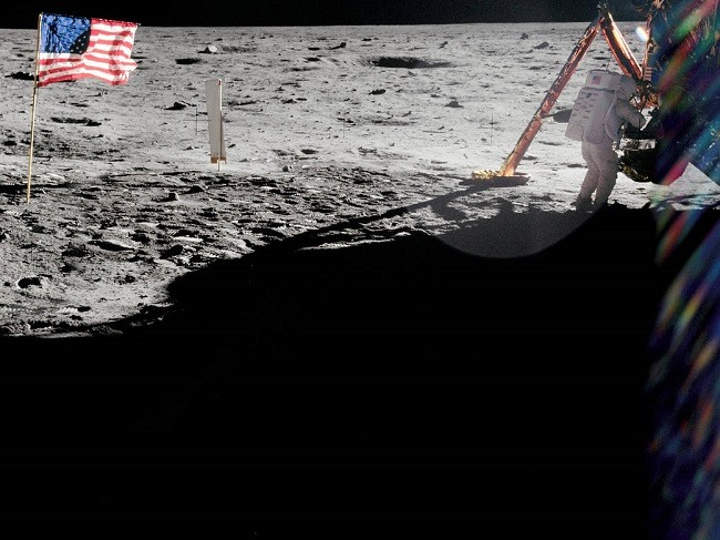 Off-centre shot of Neil Armstrong working on the lunar lander with the US flag in the top left of frame.