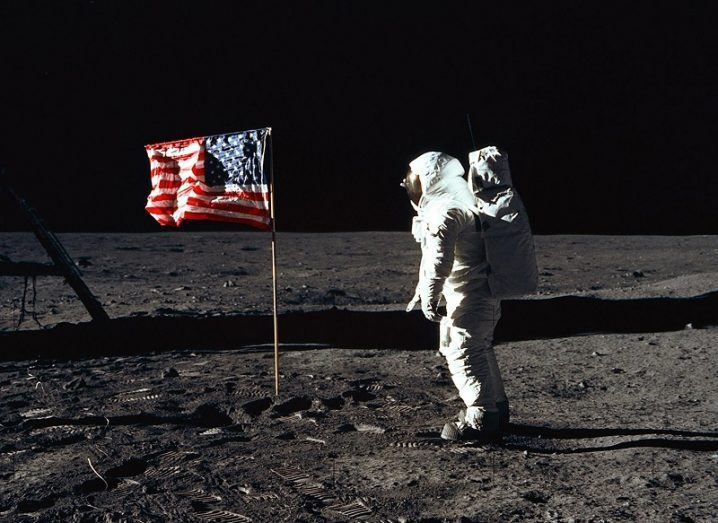 Buzz Aldrin in his spacesuit posing beside the US flag on the moon against the blackness of space.
