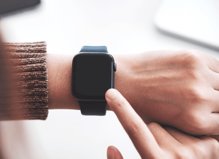 The wrist of a person wearing a light brown jumper and an Apple Watch.