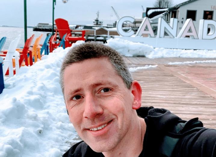 Selfie taken by Barry McDermott smiling against a snowy backdrop and wooden boardwalk.