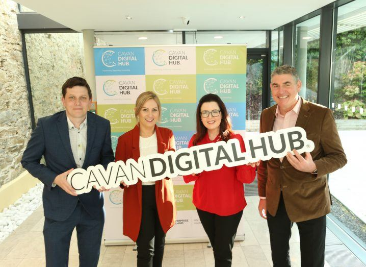 """Four people hold a sign that reads """"Cavan Digital Hub""""."""
