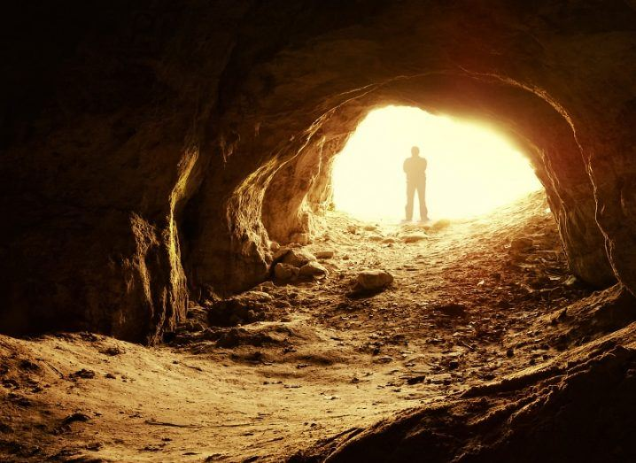 Shadow of a man standing in the entrance of a cave with yellow sunlight entering into the cave.