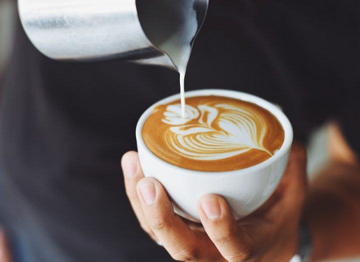 Barista with a jug of milk pouring into a cup of coffee.