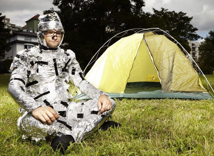 Man totally covered in tin foil sitting cross legged on grass beside a small pop-up tent.