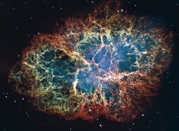 The crab nebula coloured blue, red and yellow against a starry background.